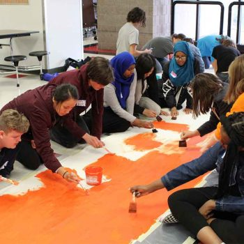 Students paint a banner in the orange color of the MN Can't Wait coalition.