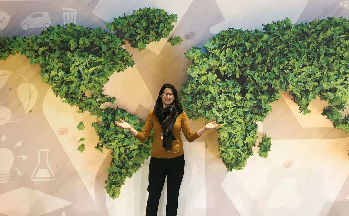 Alexis in front of map of world made of plants