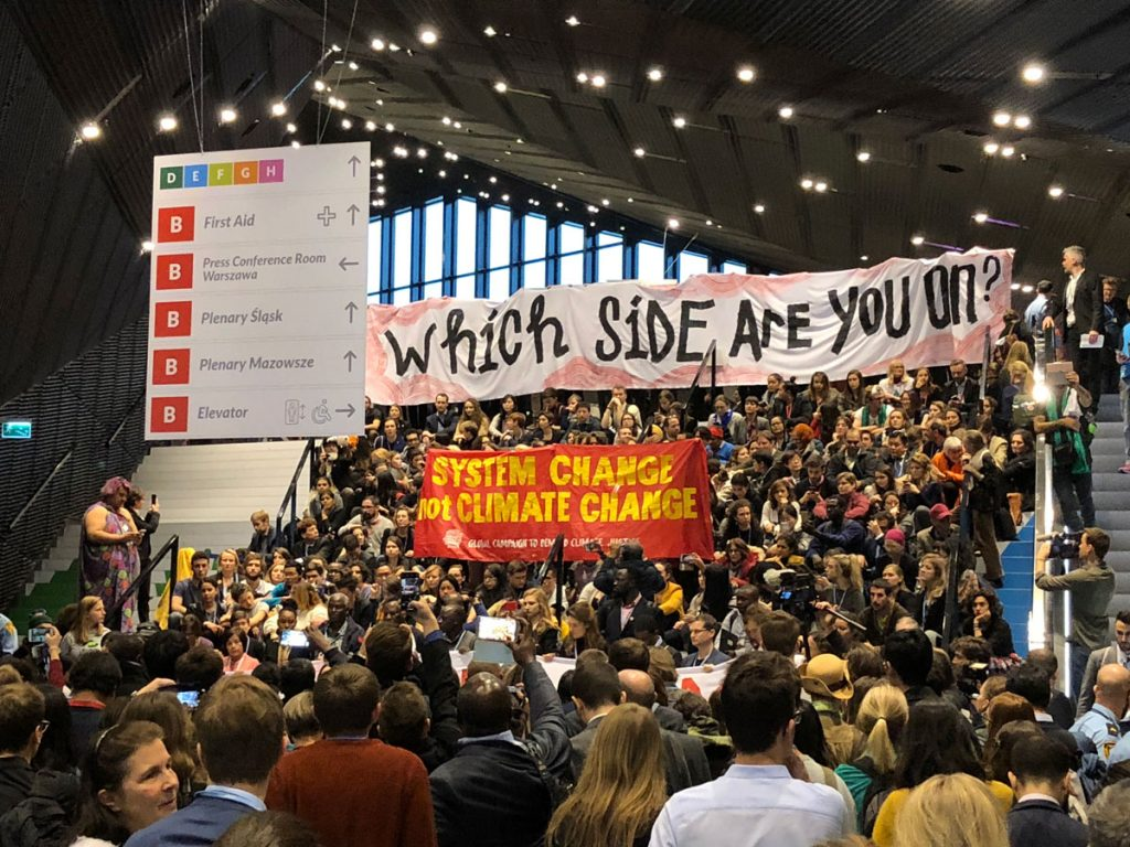 Protesters holding signs at COP24