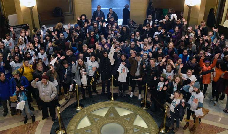 Youth smile with their hands raised in the Capitol rotunda