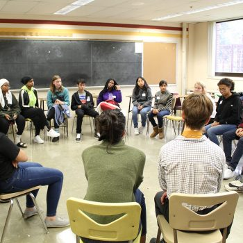 Youth in a circle discuss climate change solutions.