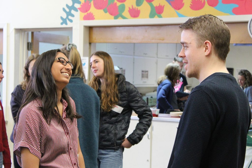 A student and teacher from different schools smile and chat.