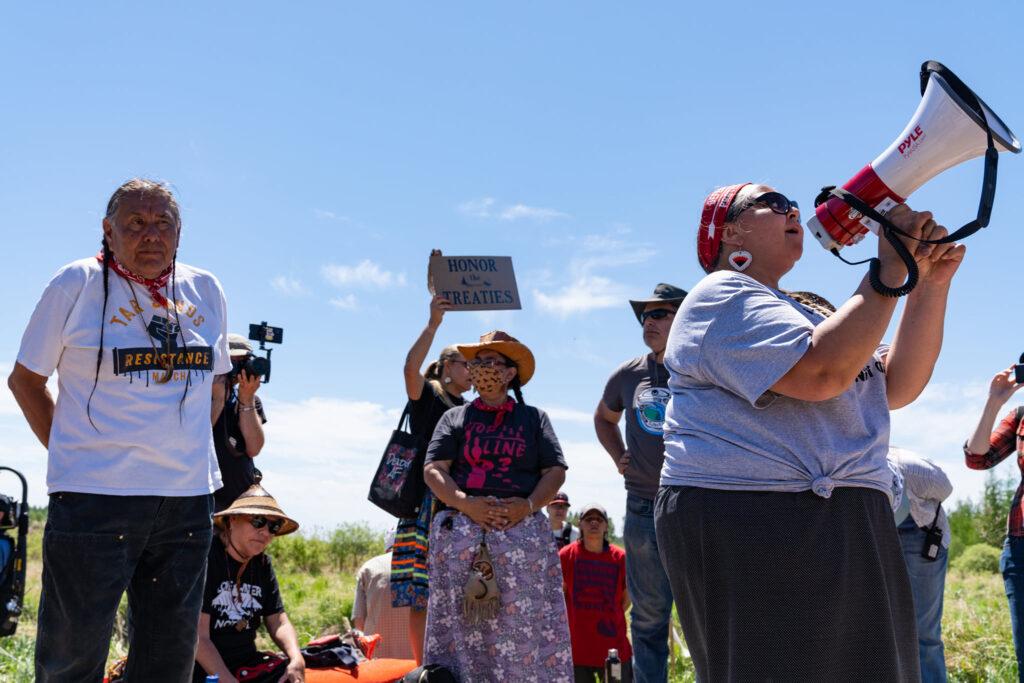 Indigenous water protectors listen as someone speaks in a megaphone.