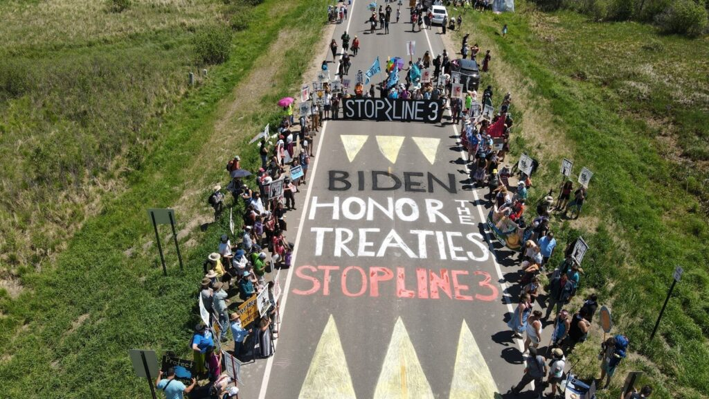 Dozens of people line and block a road. The street is painted with the message: Biden Honor the Treaties, Stop Line 3.
